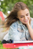 Giovane studente sorridente che studia sull'erba Fotografia Stock