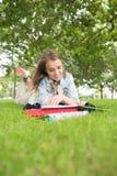 Giovane studente sorridente che studia sull'erba Immagine Stock Libera da Diritti