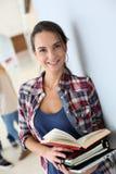 Giovane studente sorridente con i libri nel corridoio Fotografia Stock