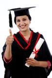 Giovane studente sorridente di graduazione che fa gesto del thumbsup Fotografia Stock