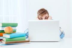Giovane studente sveglio che per mezzo del computer portatile Fotografia Stock