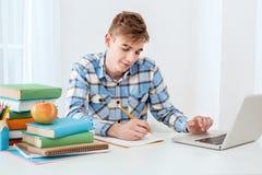 Giovane studente sveglio che per mezzo del computer portatile Fotografie Stock