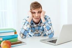 Giovane studente sveglio che per mezzo del computer portatile Fotografie Stock Libere da Diritti