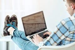 Giovane studente sveglio che per mezzo del computer portatile Immagini Stock