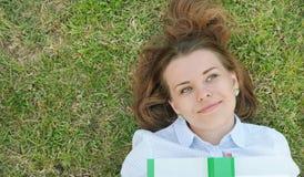 Giovane studente sveglio con il libro che si trova sull'erba nel parco Fotografia Stock