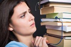 Giovane studente triste che tiene molti libri Fotografie Stock Libere da Diritti