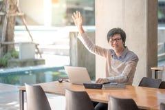 Giovane studente universitario asiatico che solleva la sua mano Fotografia Stock