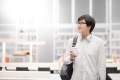 Giovane studente universitario asiatico dell'uomo in biblioteca Immagini Stock