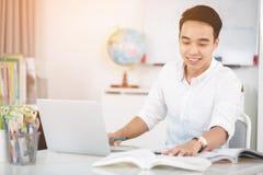 Giovane studente universitario asiatico dell'uomo che lavora con il computer portatile Immagine Stock