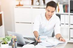 Giovane studente universitario asiatico dell'uomo che lavora con il computer portatile Fotografia Stock
