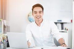 Giovane studente universitario asiatico dell'uomo che lavora con il computer portatile Immagini Stock