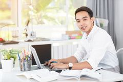 Giovane studente universitario asiatico dell'uomo che lavora con il computer portatile Fotografie Stock