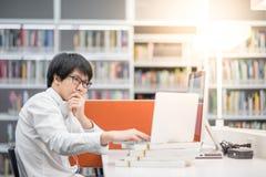 Giovane studente universitario asiatico dell'uomo che lavora nella biblioteca Immagini Stock
