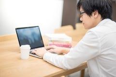 Giovane studente universitario asiatico dell'uomo che lavora nella biblioteca Fotografia Stock