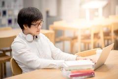 Giovane studente universitario asiatico dell'uomo che lavora nella biblioteca Fotografia Stock Libera da Diritti