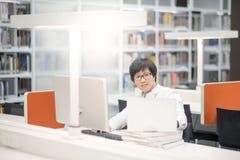 Giovane studente universitario asiatico dell'uomo che lavora nella biblioteca Fotografie Stock Libere da Diritti