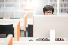 Giovane studente universitario asiatico dell'uomo che per mezzo del computer Fotografia Stock