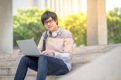Giovane studente universitario asiatico dell'uomo che si siede sulla scala Fotografia Stock