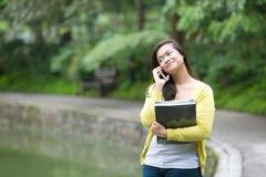 Giovane studente universitario asiatico sul telefono in parco Fotografia Stock