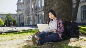 Giovane studente universitario che per mezzo del computer portatile con il sorriso sul fronte, sedentesi sotto l'albero Immagine Stock