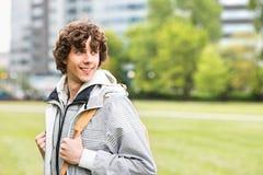 Giovane studente universitario maschio sorridente alla città universitaria dell'istituto universitario Fotografia Stock Libera da Diritti