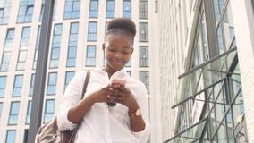 Giovane studentessa africana felice in camicia di base bianca con lo zaino di cuoio che esamina il suo smartphone video d archivio