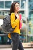 Giovane studentessa attraente che cammina per classificare con la borsa di libro Immagine Stock Libera da Diritti