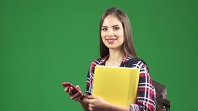 Giovane studentessa attraente che per mezzo del suo Smart Phone che sorride alla macchina fotografica fotografia stock