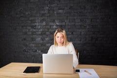 Giovane studentessa bionda che impara online con il computer portatile che si siede nell'interno moderno Immagine Stock Libera da Diritti