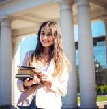 Giovane studentessa caucasica con i libri sulla città universitaria Fotografie Stock