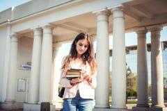 Giovane studentessa caucasica con i libri sulla città universitaria Immagini Stock Libere da Diritti