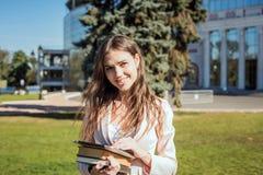 Giovane studentessa caucasica con i libri sulla città universitaria Immagine Stock