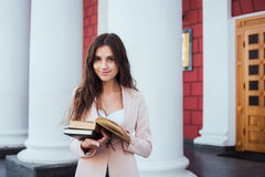 Giovane studentessa caucasica con i libri sulla città universitaria Immagine Stock Libera da Diritti