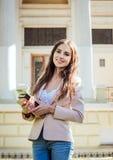 Giovane studentessa caucasica con i libri sulla città universitaria Fotografie Stock Libere da Diritti