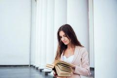 Giovane studentessa caucasica con i libri sulla città universitaria Fotografia Stock