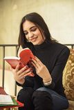 Giovane studentessa che legge un libro in un caffè Fotografie Stock