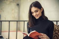 Giovane studentessa che legge un libro in un caffè Immagine Stock