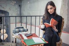 Giovane studentessa che legge un libro in un caffè Fotografia Stock Libera da Diritti