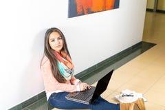 Giovane studentessa che per mezzo del computer portatile Fotografie Stock Libere da Diritti