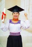 Giovane studentessa che porta blusa ed il cappello tradizionali di graduazione, tenendo diploma acciambellato, sorridente fiero p Fotografia Stock