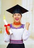 Giovane studentessa che porta blusa ed il cappello tradizionali di graduazione, tenendo diploma acciambellato, sorridente fiero p Fotografie Stock Libere da Diritti