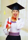 Giovane studentessa che porta blusa ed il cappello tradizionali di graduazione, tenendo diploma acciambellato, sorridente fiero p Immagini Stock