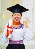 Giovane studentessa che porta blusa ed il cappello tradizionali di graduazione, tenendo diploma acciambellato, sorridente fiero p Fotografie Stock