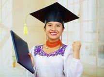 Giovane studentessa che porta blusa ed il cappello tradizionali di graduazione, tenendo il libretto nero del diploma, sorridente  Immagini Stock Libere da Diritti