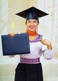 Giovane studentessa che porta blusa ed il cappello tradizionali di graduazione, tenendo il libretto nero del diploma, sorridente  Immagine Stock