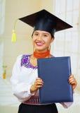 Giovane studentessa che porta blusa ed il cappello tradizionali di graduazione, tenendo il libretto nero del diploma, sorridente  Fotografia Stock