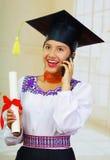 Giovane studentessa che porta blusa tradizionale con il cappello di graduazione, tenente il rotolo di carta convenzionale del dip Fotografie Stock