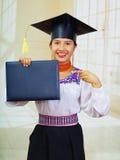 Giovane studentessa che porta blusa tradizionale ed il cappello di graduazione, tenenti il libretto nero del diploma mentre indic Fotografie Stock