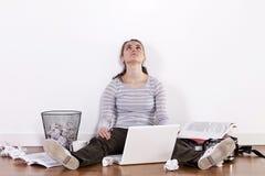 Giovane studentessa che si siede sul pavimento circondato dai libri e dall'ammasso Immagine Stock