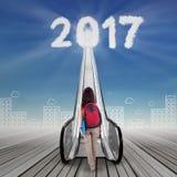 Giovane studentessa con i numeri 2017 e la scala mobile Fotografia Stock